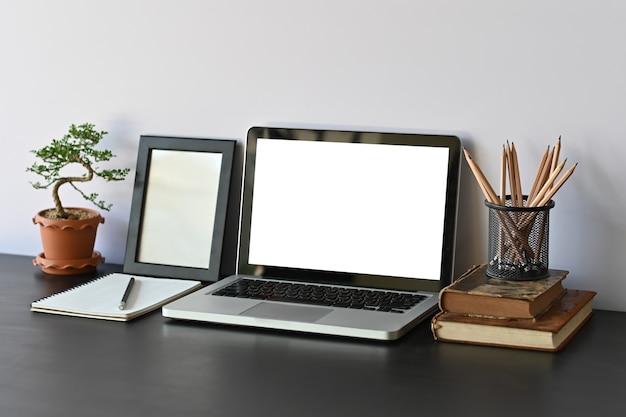Computadora portátil, libros, lápiz, marco de fotos y bonsáis en el escritorio de office. Foto Premium