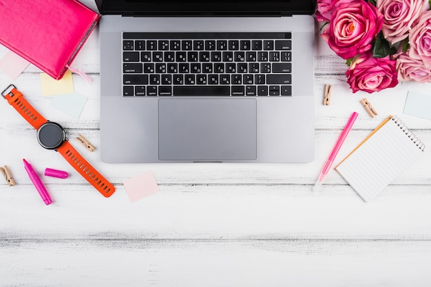 Computadora portatil plana con ramo de rosas rosadas. Foto gratis
