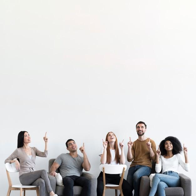 Comunidad de jóvenes con los dedos apuntando hacia arriba. Foto gratis