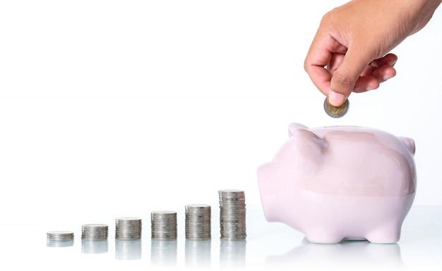 El concepto de ahorrar dinero, mano que pone una moneda en la hucha en blanco Foto Premium