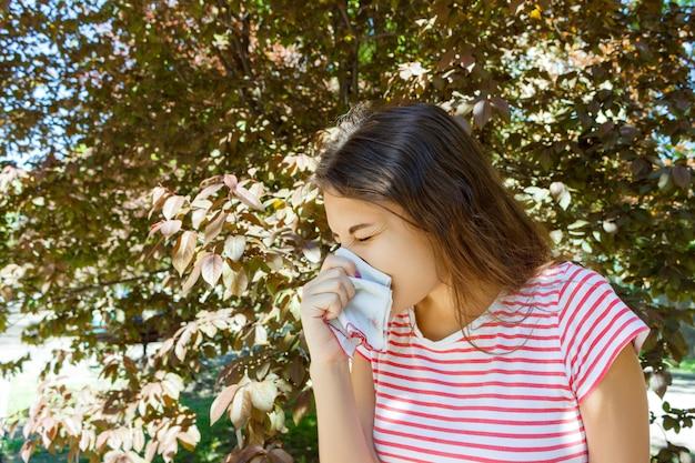 Concepto de alergia. chica joven que estornuda con el limpiador de la nariz entre árboles florecientes en parque Foto Premium