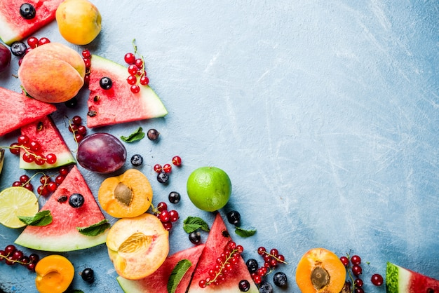 Concepto de alimentos vitamínicos, varias frutas y bayas sandía melocotón menta ciruela albaricoques grosella de arándanos Foto Premium