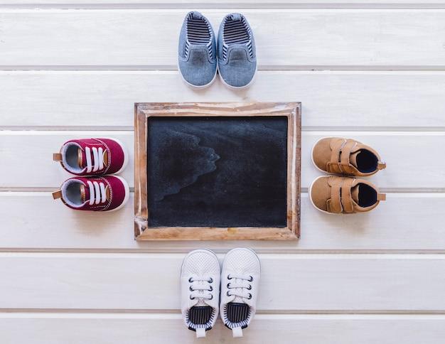 Concepto de bebé con cuatro pares de zapatos y pizarra Foto gratis