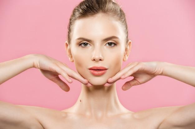 Concepto de belleza - close up retrato de niña caucásica atractiva con la piel de belleza natural aislado en fondo de color rosa con copia espacio. Foto gratis