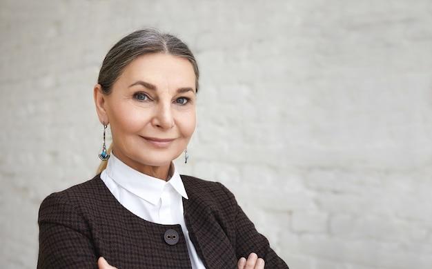 Concepto de belleza, estilo, moda y edad. close up retrato de positivo elegante mujer de 60 años con cabello gris y rostro arrugado posando contra la pared de ladrillo blanco. Foto gratis