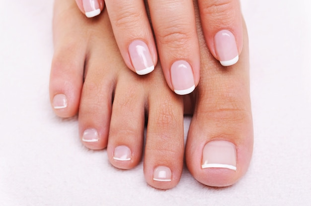 Concepto de uñas de belleza de una mano y pies femeninos con hermosa manicura y pedicura francesa Foto gratis