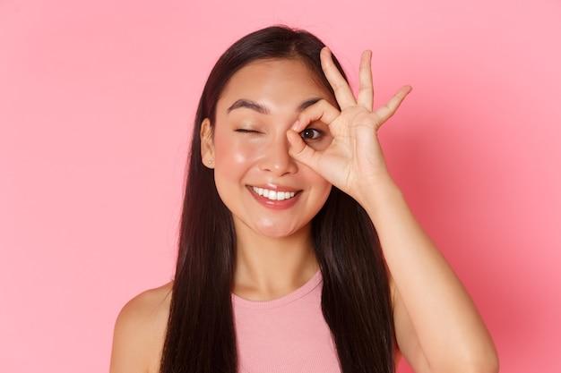 Concepto de belleza, moda y estilo de vida. retrato de una chica asiática atractiva kawaii que muestra un gesto bien sobre el ojo y un guiño despreocupado, sonriendo complacido, garantía de calidad, lugar recomendado Foto Premium