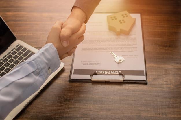 El concepto de bienes raíces, la agencia bancaria se da la mano con el cliente o el comprador de la casa después de una comunicación exitosa y firma el contrato Foto Premium