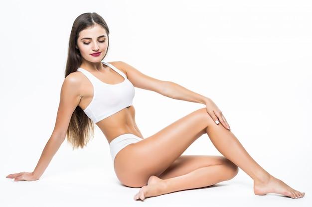 Concepto de bienestar y belleza. hermosa mujer delgada en ropa interior blanca sentada en el piso blanco Foto gratis
