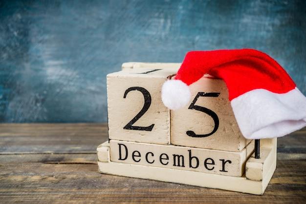 Concepto de celebración de navidad, antiguo calendario de madera de estilo retro con sombrero rojo de santa Foto Premium