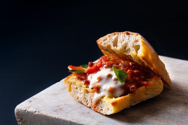 Concepto de comida casera a la parrilla boloñesa orgánica sándwich de pan artesanal en negro Foto Premium