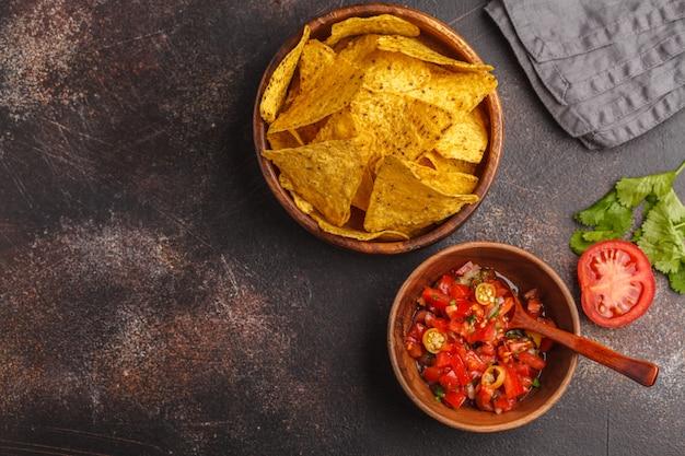 Concepto de comida mexicana. nachos: totopos de maíz amarillo con salsa de tomate pico del gallo, vista superior, espacio de copia. Foto Premium