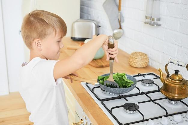 Concepto de comida, niños y cocina. retrato de guapo colegial en camiseta blanca de pie en el mostrador de la cocina con estufa para cocinar la cena, sosteniendo el tornero de metal, guisado de hojas verdes en una sartén Foto gratis
