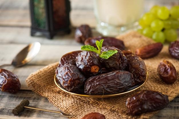 El concepto de comida de ramadán. linterna de ramadán con leche, dátiles frutales, uva y hojas de menta. Foto Premium