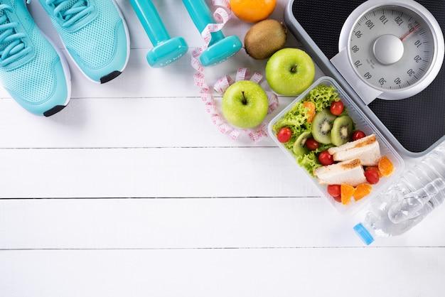 Concepto de comida sana y deporte sobre fondo blanco de madera. Foto Premium