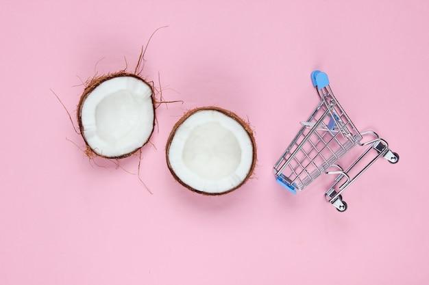 Concepto de compra de frutas. carrito de la compra, mitades de coco roto sobre un fondo rosa. Foto Premium