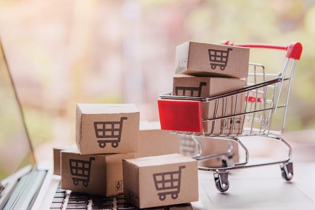 Concepto de compras en línea: paquetes o cajas de papel con el logotipo de un carrito de compras en un carrito en un teclado portátil. servicio de compras en la web en línea. ofrece servicio a domicilio. Foto Premium