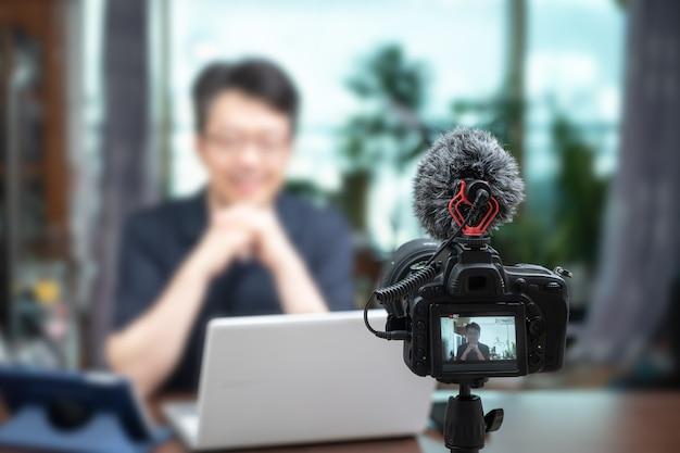 Concepto de conferencia en línea. hombre asiático de mediana edad dando conferencias en línea en casa. Foto Premium