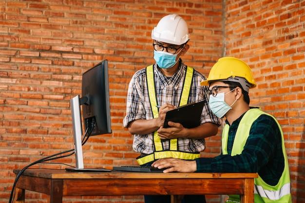 El concepto de construcción de ingeniero y arquitecto es usar máscaras médicas que trabajen en el sitio de construcción a través del monitor para su revisión debido al impacto global de covid-19 y el distanciamiento social. Foto Premium