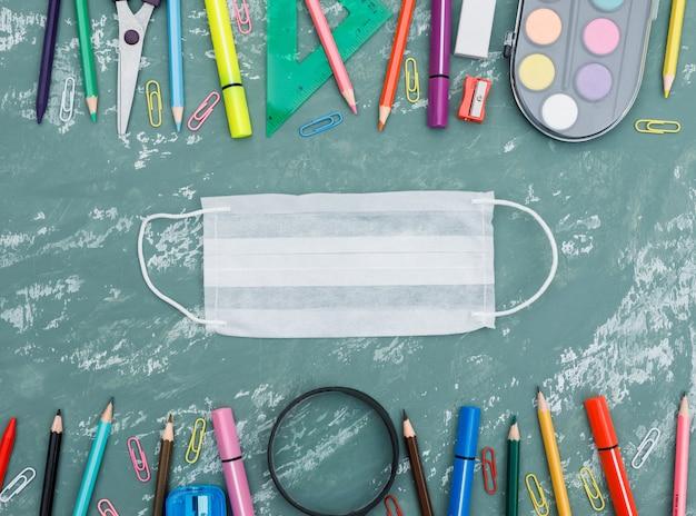 Concepto de cuarentena escolar con máscara médica, lupa, útiles escolares sobre fondo plano de yeso. Foto gratis