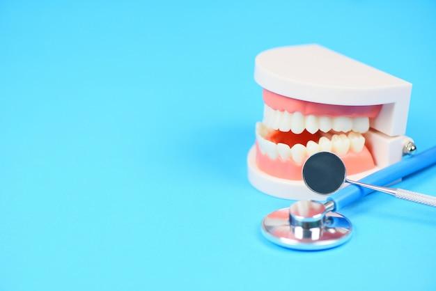 Concepto de cuidado dental: herramientas de dentista con prótesis dentales, instrumentos de odontología e higiene dental y chequeo de equipos con modelo de dientes y espejo bucal de salud bucal Foto Premium