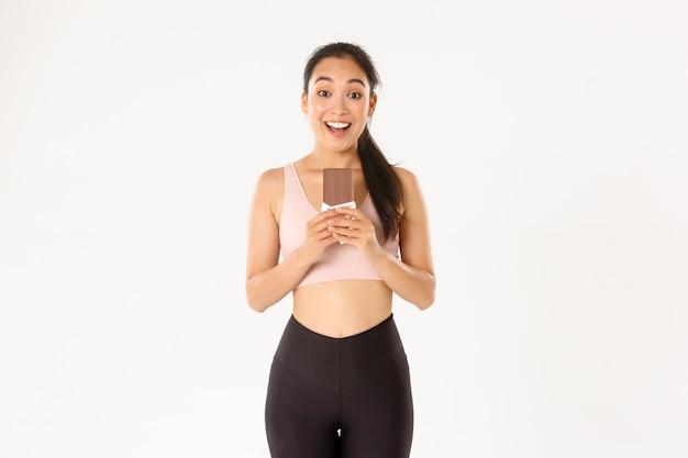 Concepto de deporte, bienestar y estilo de vida activo. feliz sonriente atleta femenina asiática con proteína de chocolate mala y con aspecto emocionado, comiendo dulces saludables para un entrenamiento prolongado. Foto gratis