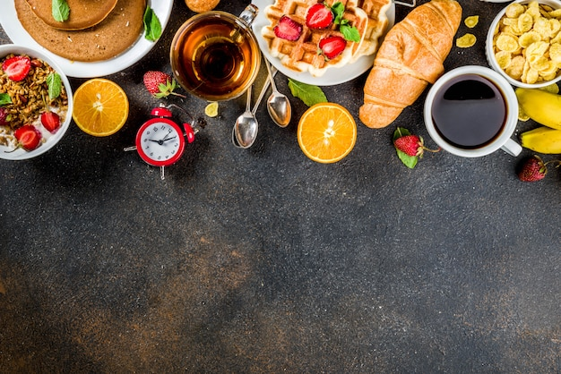 Concepto de desayuno saludable, varios alimentos de la mañana: panqueques, waffles, sándwich de avena con croissant y granola con yogur, fruta, bayas, café, té, fondo de jugo de naranja Foto Premium