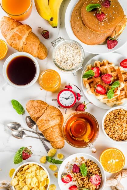 Concepto de desayuno saludable, varios alimentos de la mañana: panqueques, waffles, sándwich de avena con croissant y granola con yogur, fruta, bayas, café, té, jugo de naranja, fondo blanco Foto Premium