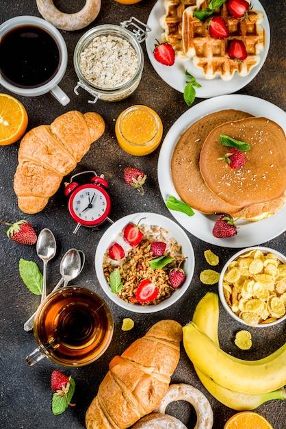 Concepto de desayuno saludable, varios alimentos de la mañana: panqueques, waffles, sándwich de avena con cruasanes y granola con yogur, fruta, bayas, café, té, jugo de naranja Foto Premium