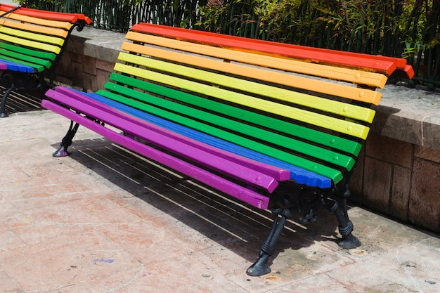 Concepto del día del orgullo. banco de madera pintado en colores del arco iris en un parque Foto Premium