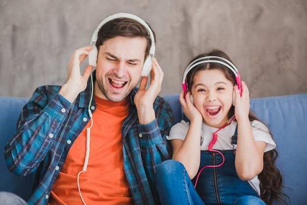 Concepto para el día del padre con padre e hija escuchando música Foto gratis