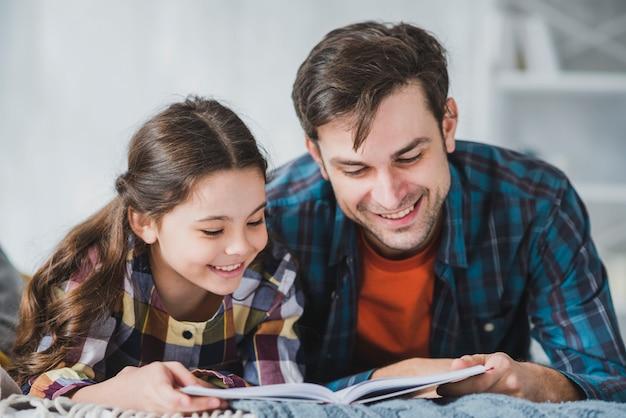 Concepto para el día del padre con padre e hija leyendo Foto Premium