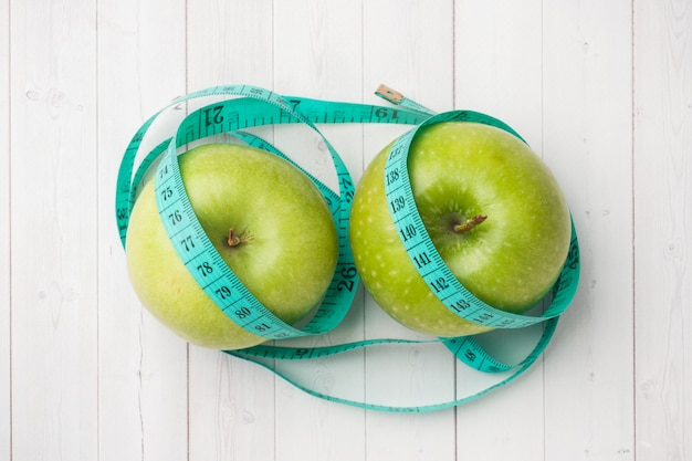Concepto de dieta dos manzanas verdes y una rueda de ruleta en una tabla blanca. Foto Premium