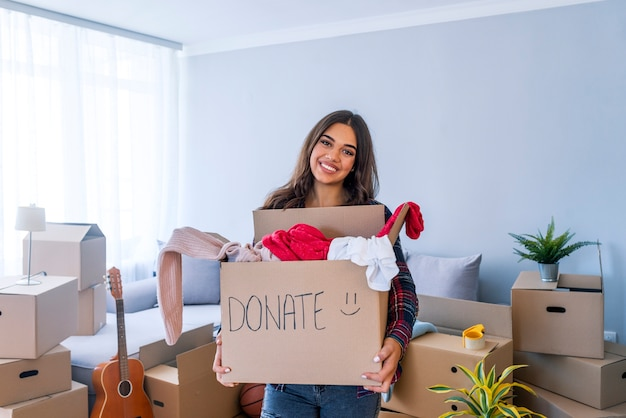 Mujer con caja para donar ropa