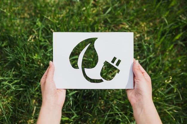 Concepto eco con manos sujetando papel cortando que muestra energía eco Foto gratis