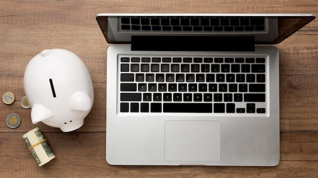 Concepto de economía con hucha y laptop Foto gratis