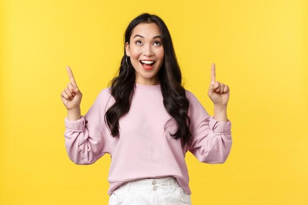 Concepto de emociones, estilo de vida y moda de personas. entusiasta feliz mujer atractiva sonriendo, reaccionar alegre ante increíbles descuentos u oferta especial en la pancarta superior, apuntando con los dedos hacia arriba Foto Premium