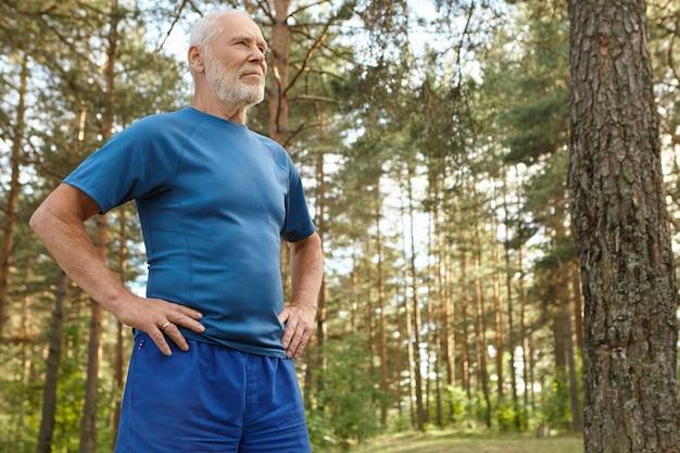 Concepto de energía, salud, bienestar, actividad y deporte. hombre senior atlético de ajuste concentrado en ropa deportiva manteniendo las manos en la cintura disfrutando de ejercicios físicos en el bosque, de pie entre pinos Foto gratis