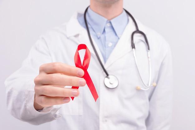 Concepto de enfermedad oncológica. doctor con bata blanca y estetoscopio con cinta roja como símbolo de ayudas. Foto Premium