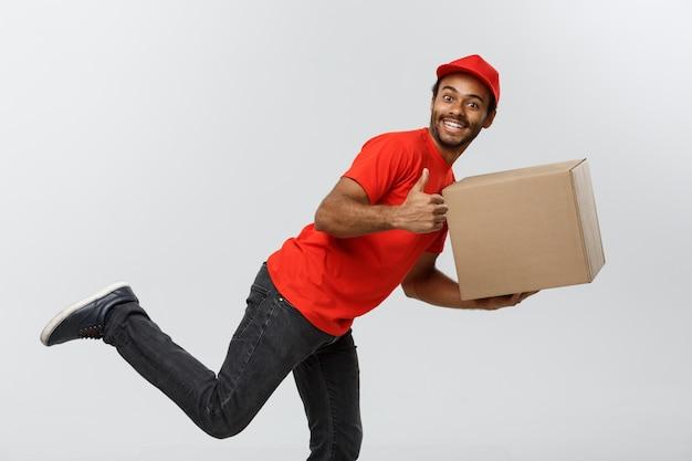 Concepto de entrega - guapo afroamericano hombre de entrega corriendo para entregar un paquete para el cliente. aislado en el estudio de fondo gris. espacio de la copia. Foto gratis