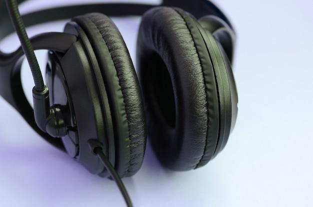 Concepto de escuchar música. auriculares negros se encuentra en el fondo violeta Foto Premium