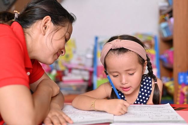 Concepto de escuela en casa, niños asiáticos y madre enseñan a hacer la tarea escolar Foto Premium