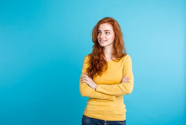 Concepto de estilo de vida - close up retrato joven hermosa atractiva jengibre pelo rojo chica jugando con su cabello con timidez. fondo de pastel azul. copie el espacio. Foto gratis