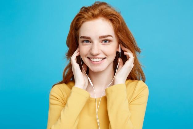 Concepto de estilo de vida - retrato de alegre alegre jengibre pelo rojo niña disfrutar de escuchar música con auriculares sonriendo alegre a la cámara. aislado en fondo azul pastel. copie el espacio. Foto Premium
