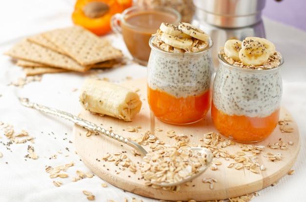 Concepto de estilo de vida saludable desayuno con café, galletas, copos de avena, pudín de chia con plátano y albaricoque Foto Premium