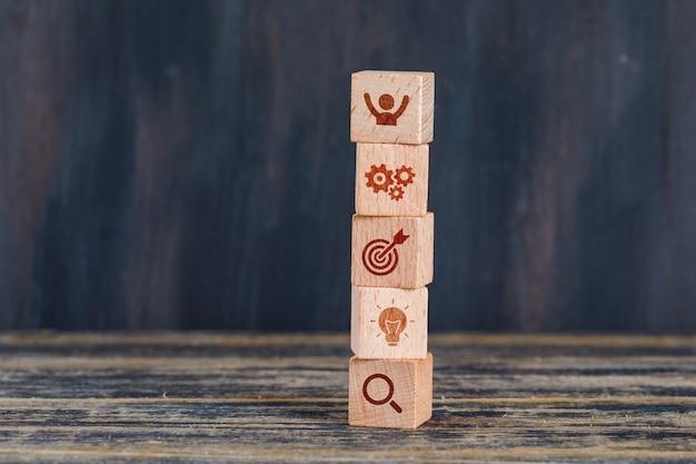 Concepto de estrategia empresarial con cubos de madera en vista lateral de fondo de madera y grunge. Foto gratis