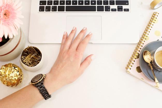 El concepto femenino del lugar de trabajo en estilo plano de la endecha con el ordenador portátil, el café, las flores, la piña de oro, el cuaderno y los clips de papel, mano de la mujer. blogger trabajando. vista superior, brillante, rosa y dorado. Foto Premium
