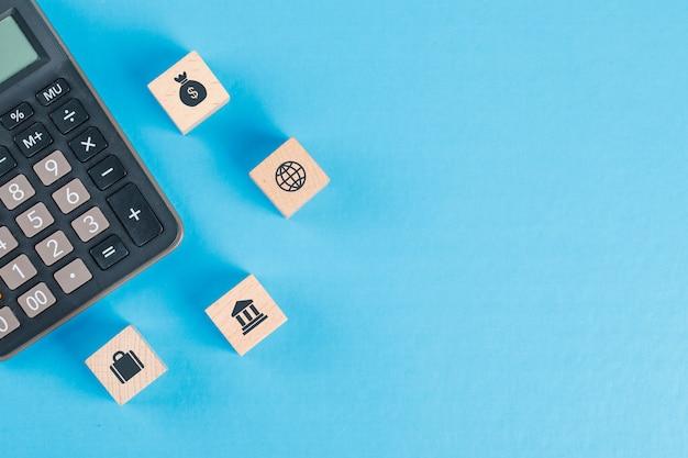 Concepto financiero con iconos en cubos de madera, calculadora en mesa azul plano lay. Foto gratis