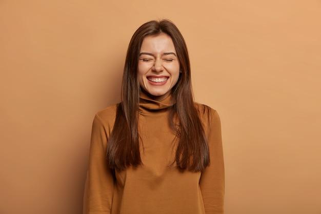 Concepto de gente y alegría. mujer adulta de cabello oscuro llena de alegría se ríe felizmente con los ojos cerrados, habla casualmente con un amigo, no puede contener la risa, usa un cuello alto informal, aislado en una pared marrón Foto gratis