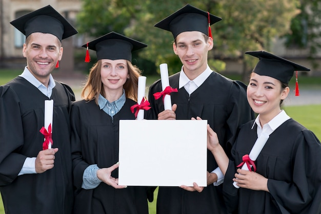 Concepto de graduación con estudiantes sujetando plantilla de certificado en blanco Foto gratis